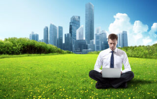 Man sitting on grass with his laptop